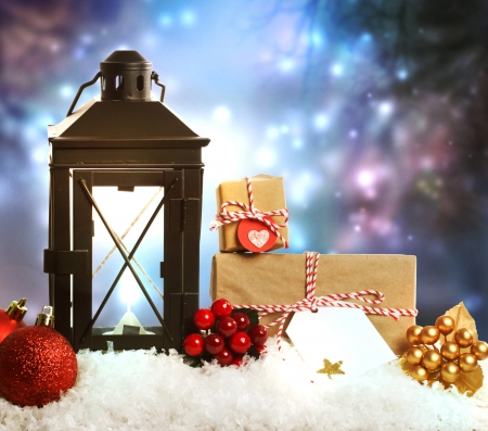 Christmas lantern with presents, ornaments and snow on a blue shinning background