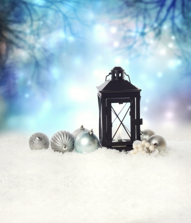 Christmas lantern and ornaments on the snow in a blue shinning night photo