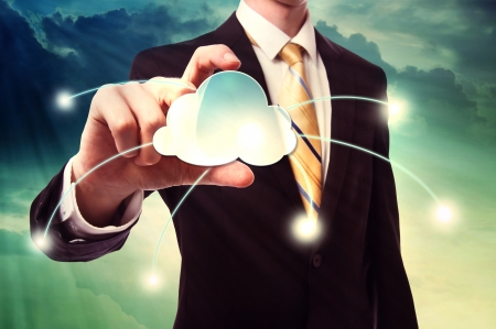cloud: Businessman holding a cloud computing icon over cloudscape background