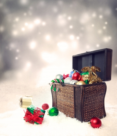 treasure box: Treasure box filled with Christmas ornaments and presents on snow Stock Photo