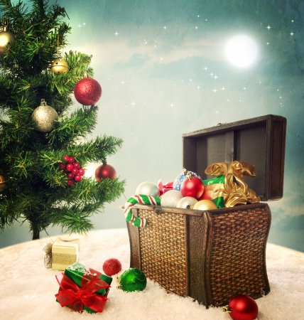 overflowing: Treasure box filled with Christmas ornaments and presents on snow with Christmas tree Stock Photo
