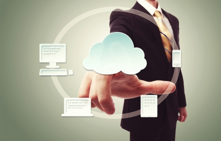 Businessman pressing cloud icon with devices over vintage green background photo