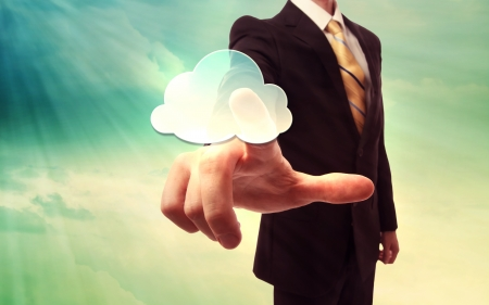 Businessman pressing a cloud computing icon on blue and yellow sky background