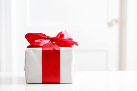 Gift box with red bow on the white table