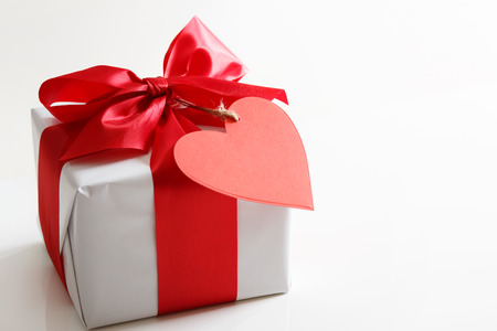 Gift box with red satin ribbon and heart tag photo
