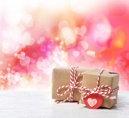 Small handmade gift boxes in pink hearts background photo