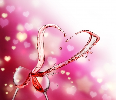 Heart splash from two glasses of red wine on abstract small heart lights background photo