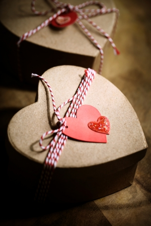 Gift boxes with handmade heart tags on wooden board photo