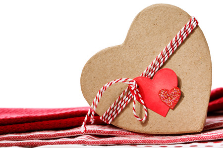 Heart shaped gift box with heart tag on red table cloth photo