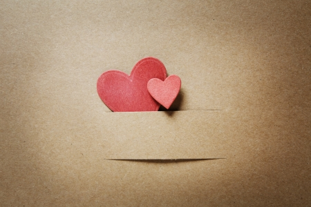 Small paper cut red hearts on earthy colored paper Stock Photo