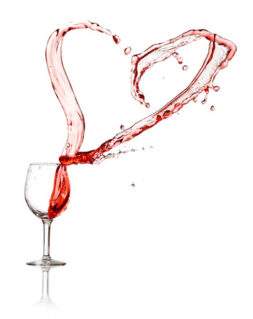 Heart splash from a glass of red wine isolated on white background photo