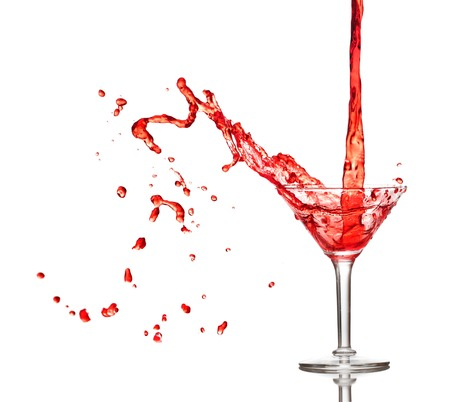 Red cocktail splashing from glass isolated on white  photo