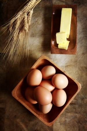Eier mit Butter und Weizen auf rustikalen Holztisch Standard-Bild - 25338934
