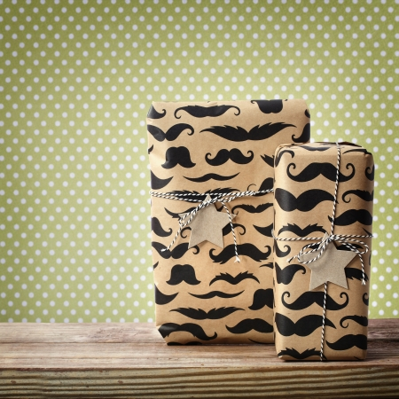 Mustache pattered gift boxes with star shaped tags over polka dots background
