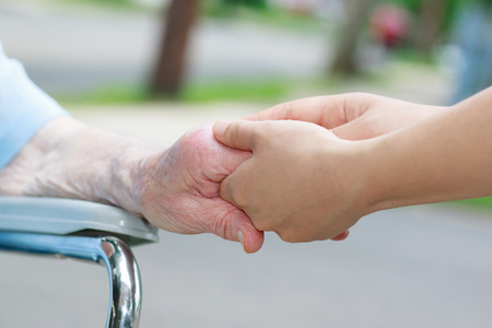 Caregiver holding an elderly womans hand outside photo