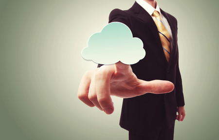 Businessman pushing a cloud icon over green vintage background photo