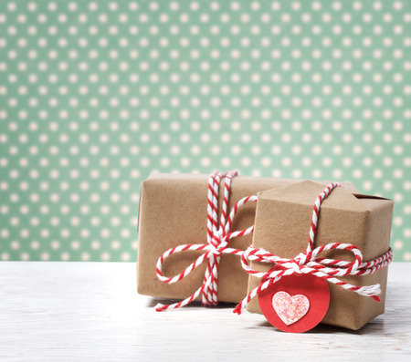 Handmade gift boxes with heart tag on polka dots background photo
