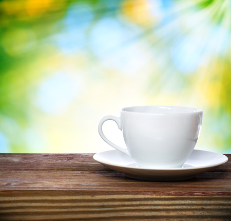 forest tea: Coffee cup on shiny green with sunshine background