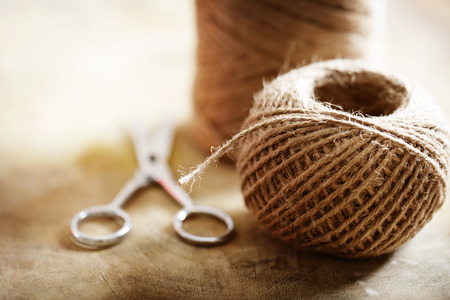 crafted: Twine cord with scissors on rustic wooden table