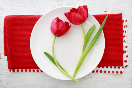 Two red tulips on white plate on red napkins photo