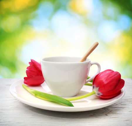 Coffee cup with red tulips in shiny leaves background photo