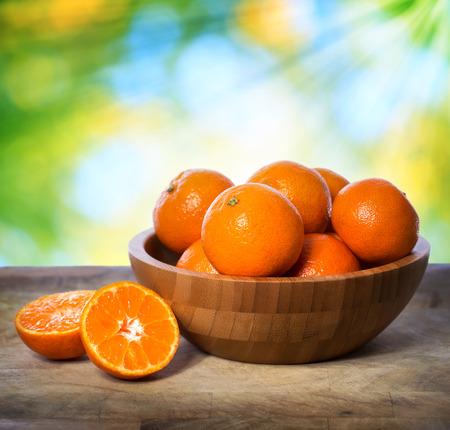 mandarin oranges: Tangerines in wooden bowl over shiny leaves background Stock Photo