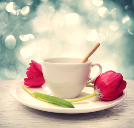coffee table: Coffee cup with red tulips over blue shiny background