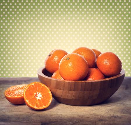 mandarin oranges: Tangerines in wooden bowl over green polka dots background