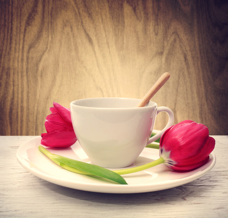 coffee table: Coffee cup with red tulips over wooden wall background