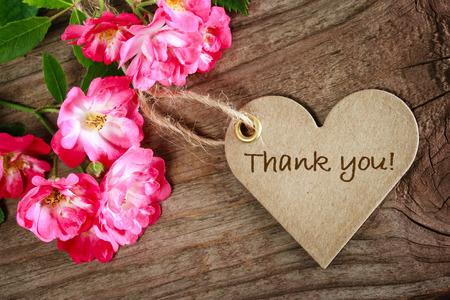 agradecimiento: Coraz�n en forma de tarjeta de agradecimiento con flores sobre fondo de madera