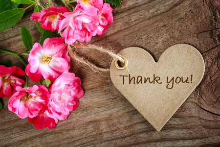 gratefulness: Heart shaped thank you card with flowers on wood background
