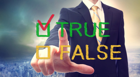 falso: Empresario apuntando a casilla VERDADERO o FALSO Foto de archivo