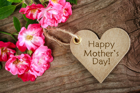 Heart shaped mothers day card with roses on wood background photo