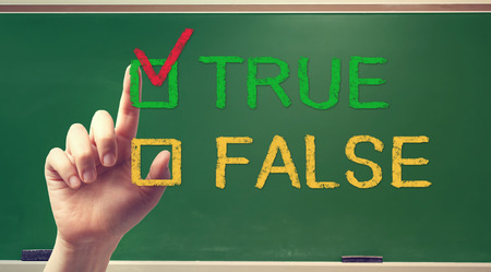 TRUE or FALSE checkbox with hand on green chalkboard photo