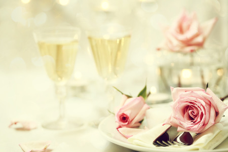 Table setting and glasses with pink roses  photo