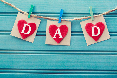 father's: Fathers day message on felt hearts over blue wooden board