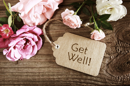 get well: Get well message tag with roses wooden table