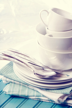 A stack of clean white plates and cups on blue napkins and wooden board Stock Photo