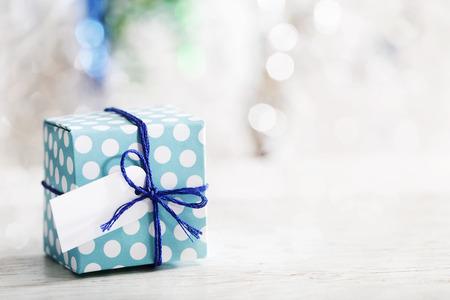 Kleine handgemaakte geschenkdoos over glanzend ornamenten Stockfoto