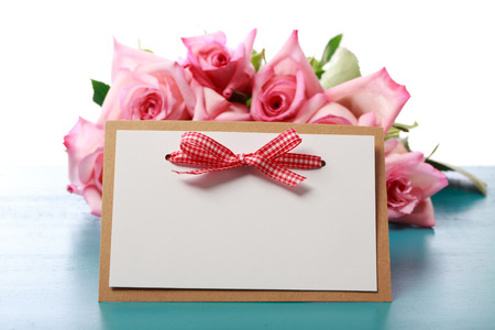 Handmade message card with pink roses on light blue colored wooden board photo
