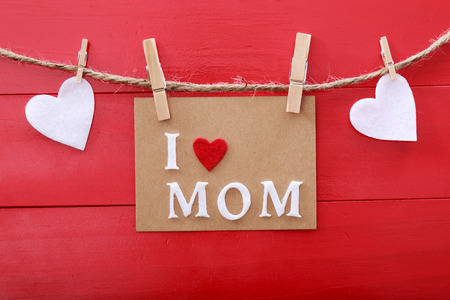 Mothers day message with felt hearts hanging with clothespins over red wooden board