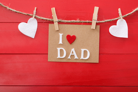 fathers day: Fathers day message with felt hearts hanging with clothespins over red wooden board