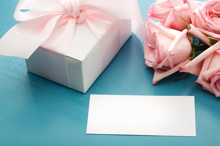 blue gift box: Blank message card with gift box and pink roses Stock Photo