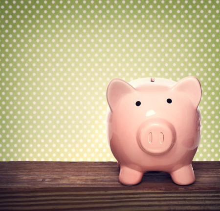 Pink piggy bank over green polka dots background Banco de Imagens - 27709233
