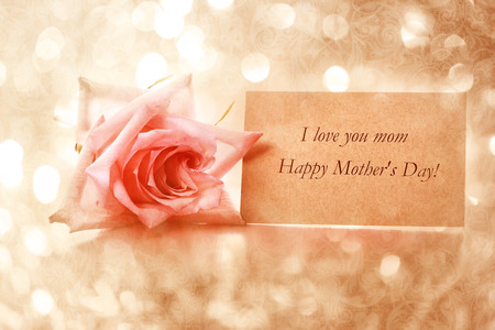 Mothers day message card with pink rose over abstract light background