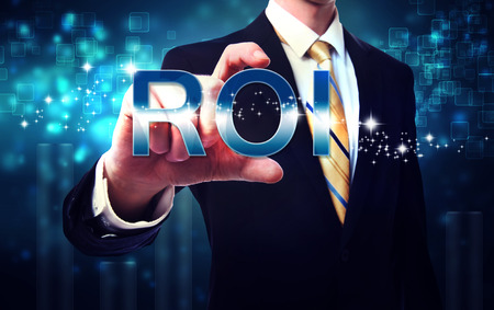 Businessman touching ROI (return on investment) on blue technology background Stock Photo