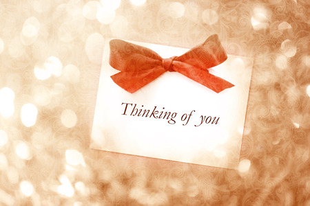 Thinking of you message with red ribbon on vintage light background photo