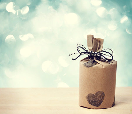 Present wrapped in a rustic earthy style on shiny blue background Stock Photo