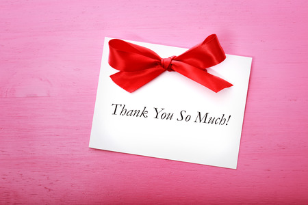 Thank you card with red ribbon on pink wooden board Stock Photo