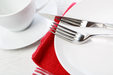 Empty coffee cup and plate on red napkins photo